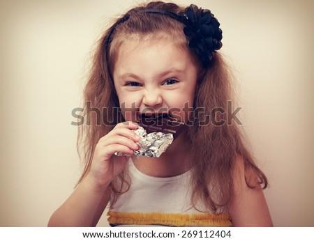 Happy fun smiling kid girl biting dark chocolate with craving eyes. Vintage closeup portrait - stock photo