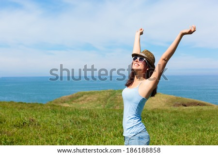 Happy funky woman enjoying freedom on travel in Asturias coast, Spain. Female on summer or spring leisure vacation raising arms to sky towards the sea. - stock photo