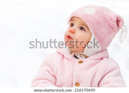 Happy funny baby in winter park. Snow is background - stock photo