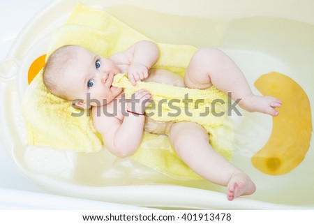 happy funny baby laughing and bathed in the bath with yellow towel