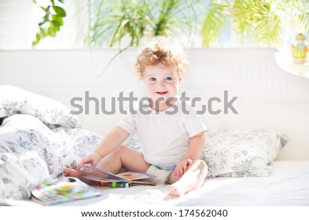 Happy funny baby reading a book in her parents bed on a sunny morning in a beautiful white bedroom with a window - stock photo