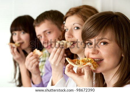 Happy funny Caucasian campaign of four people eating pizza on a light background - stock photo