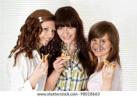 Happy funny Caucasian campaign of three people eating pizza on a light background