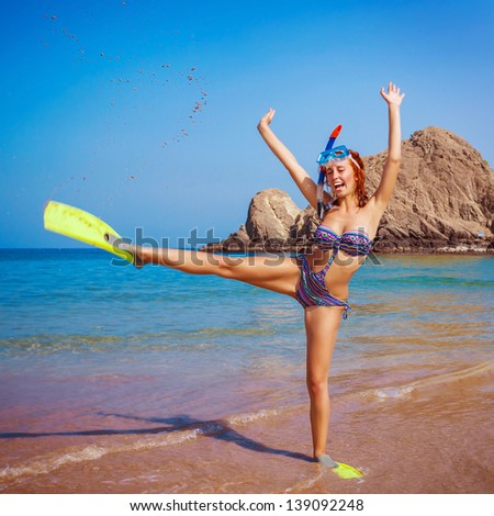 Happy funny girl wearing diving equipment, raised up hands, tropical resort, active lifestyle, summertime hobby, vacation and tourism concept - stock photo