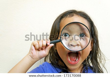 happy funny girl with magnifying glass - stock photo