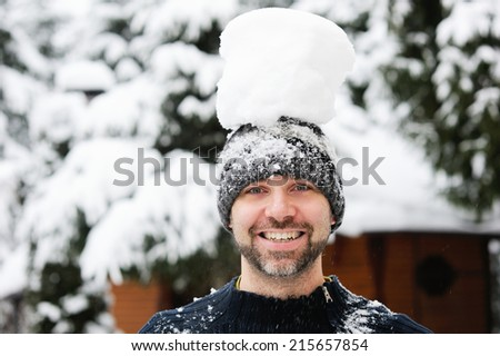 Happy funny handsome man in knit hat and sweater has fun at winter day - stock photo