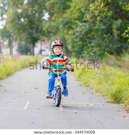 Happy funny kid boy of 4 years and colorful raincoat riding his first bike on summer day. Active leisure for children outdoors. - stock photo