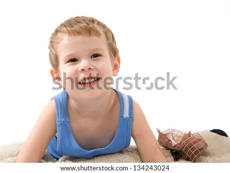 Happy funny kid lying on teddy bear - stock photo
