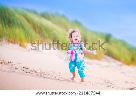 Happy funny little girl, adorable curly toddler, running and jumping in sand dunes enjoying family vacation at the North Sea, Holland, Netherlands on a hot sunny summer day at the beach - stock photo