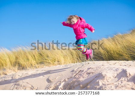 Happy funny little girl, adorable curly toddler, running and jumping in sand dunes enjoying family vacation at the North Sea, Holland, Netherlands on a sunny winter day at the beach - stock photo