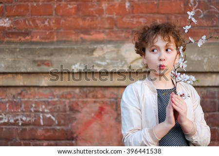 Happy, funny, little girl having fun outdoors. Adorable, cute curly child, kid fooling, making funny faces, grimaces with spring flower branch on beautiful summer day on red brick wall background. - stock photo