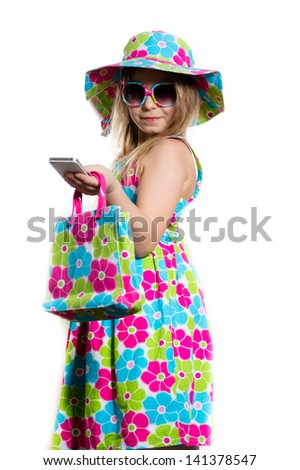 Happy funny little girl in summer colorful dress and sunglasses smiling and holding mobile phone isolated on white background