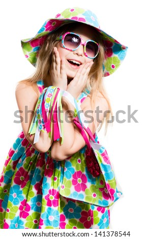 Happy funny little girl in summer colorful dress and sunglasses smiling and looking surprised isolated on white background - stock photo
