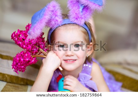 Happy funny little girl with colorful pink flowers and fancy bunny ears on head celebrates easter. Toy han in hands. - stock photo