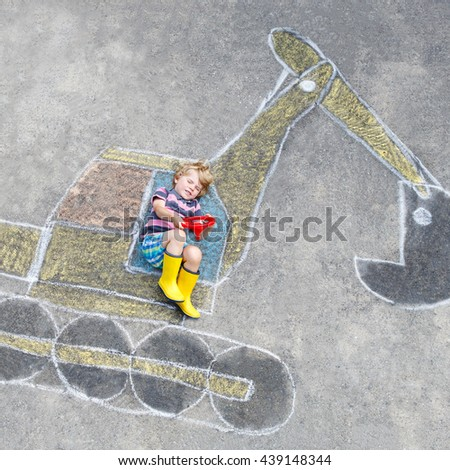 Happy funny little kid boy having fun with excavator picture drawing with colorful chalk. Creative leisure for children outdoors in summer. - stock photo