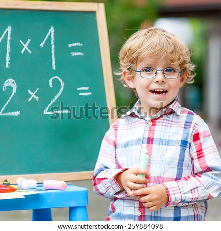 Happy funny little kid boy with glasses at blackboard practicing mathematics, outdoor. school or nursery. Back to school concept - stock photo