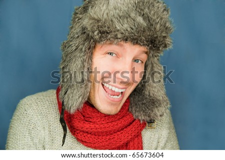 Happy funny male portrait looking snowflakes falling down wearing hat and scarf in december season - stock photo