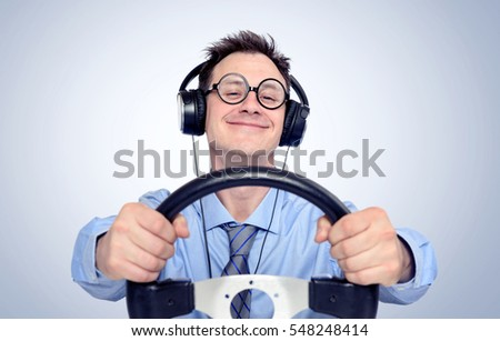 Happy funny man with glasses and headphones while driving car