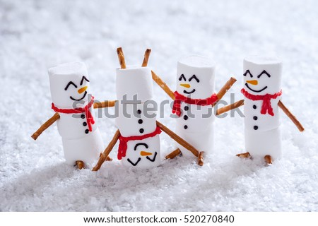 Happy funny marshmallow snowmans are having fun in snow