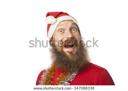 happy funny santa claus with real beard and red hat and shirt making crazy face and smiling, looking and camera. isolated on white background.