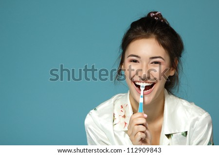 Happy funny teen girl brush her teeth. Morning theme. Over blue background.