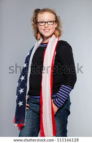 Happy funny teenage girl with curly blonde hair. Expressive face. Wearing glasses. Holding american flag. Studio shot isolated on grey background. - stock photo