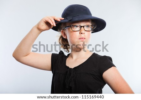 Happy funny teenage girl with curly blonde hair. Wearing glasses and blue hat. Expressive face. Studio shot isolated on grey background. - stock photo