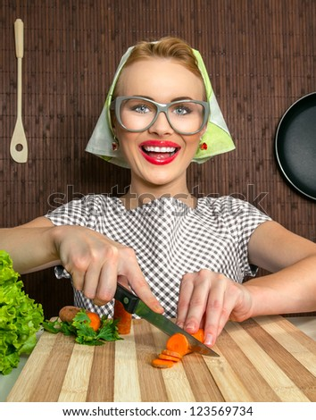 Happy funny woman cook working in the kitchen cutting carrot - stock photo