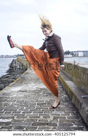 Happy Funny Woman fool of energy Jumping near the ocean on the long stone pier  - stock photo