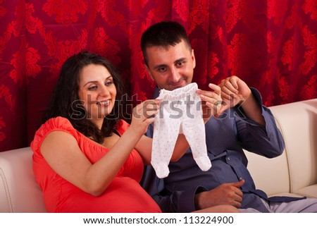 Happy future parents having conversation and holding baby cloth