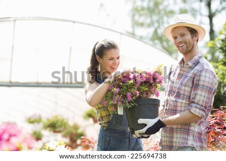 Happy gardeners holding flower pot outside greenhouse - stock photo
