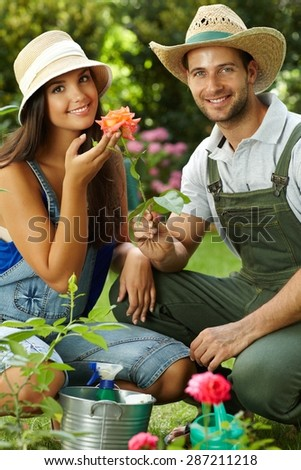 Happy gardening couple smiling at camera, smelling rose, smiling. - stock photo