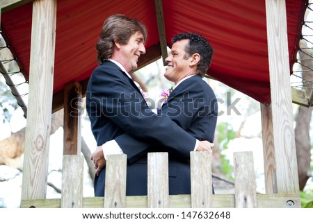 Happy gay couple getting married on the playground of a park.   - stock photo