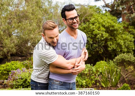 Happy gay couple hugging in garden - stock photo
