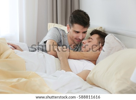 In field Happy gay couple lying in bed