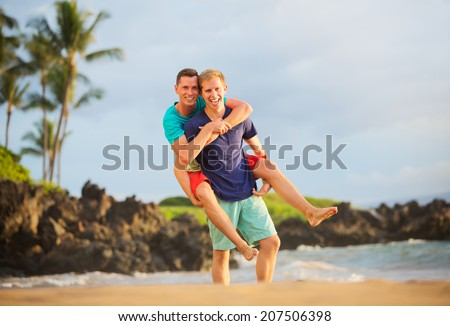 Happy gay couple on the beach - stock photo