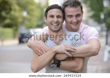 Happy gay couple outdoors hugging and smiling - stock photo