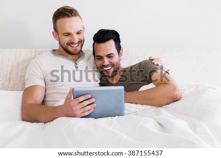 Happy gay couple using tablet in bed