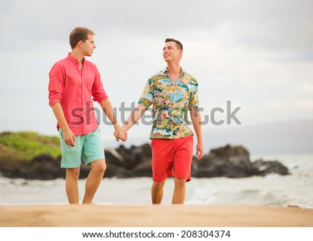 Happy gay couple walking on the beach - stock photo
