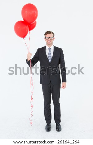 Happy geeky hipster businessman holding balloons on white background - stock photo