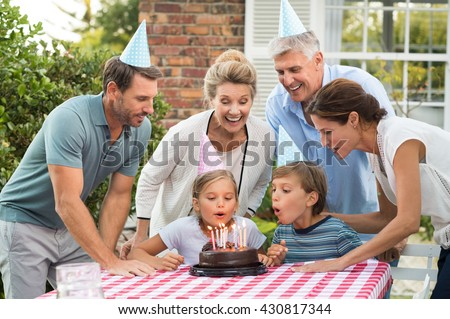 Happy generation family watching girl blowing out birthday candles at picnic table outside. Happy little girl celebrating birthday with family. Brother helping sister blow candles on her birthday. - stock photo