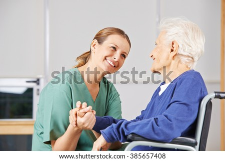 Happy geriatric nurse holding hands with senior woman in a wheelchair - stock photo