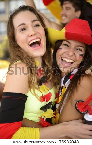 Happy German girlfriends sport soccer fans celebrating victory hugging each other. - stock photo