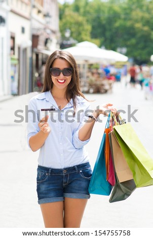 Happy girl after shopping, with credit card in hand - stock photo