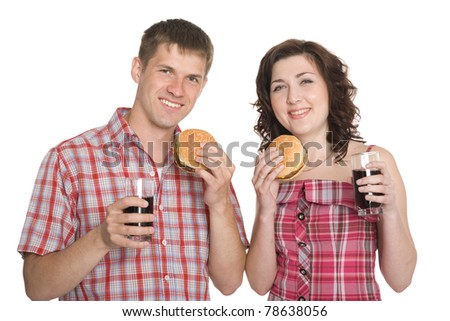 Happy girl and a guy eating hamburgers and drinking a refreshing drink. Isolated on white. - stock photo