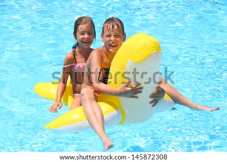 Happy girl and boy swim at the children inflatable toy in the swimming pool - stock photo