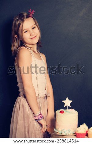 Happy girl and cupcake on birthday party - stock photo