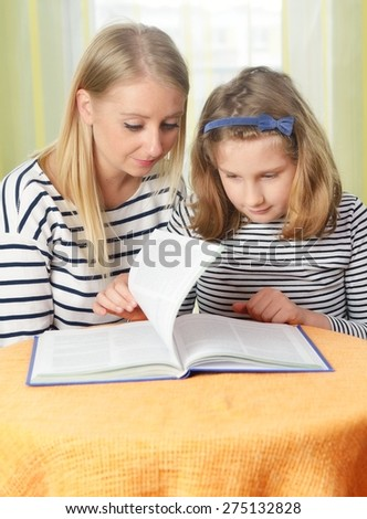 Happy girl and grandmother studying. Reading a book in home. MANY OTHER PHOTOS FROM THIS SERIES IN MY PORTFOLIO. - stock photo