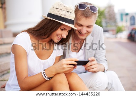 Happy girl and her boyfriend using mobile phone outside - stock photo