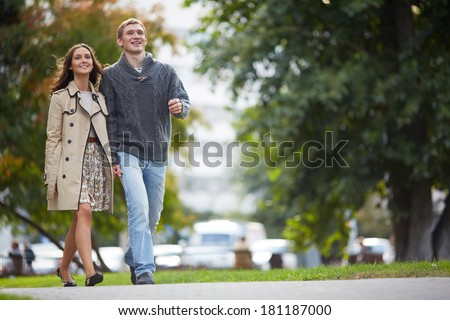 Happy girl and her boyfriend walking in park - stock photo